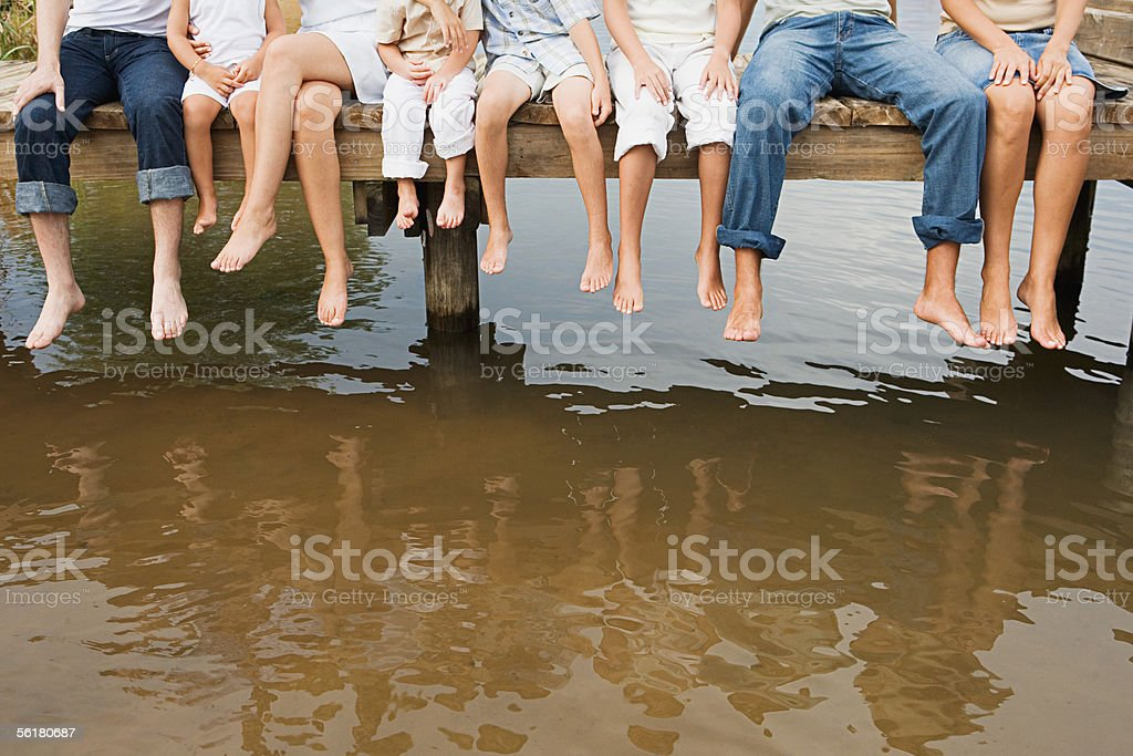 People dangling their feet off a pier stock photo