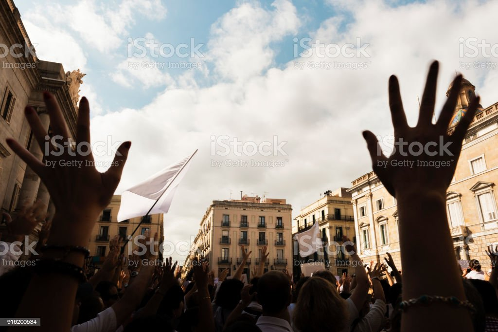 people demonstrating with hands up and flags stock photo