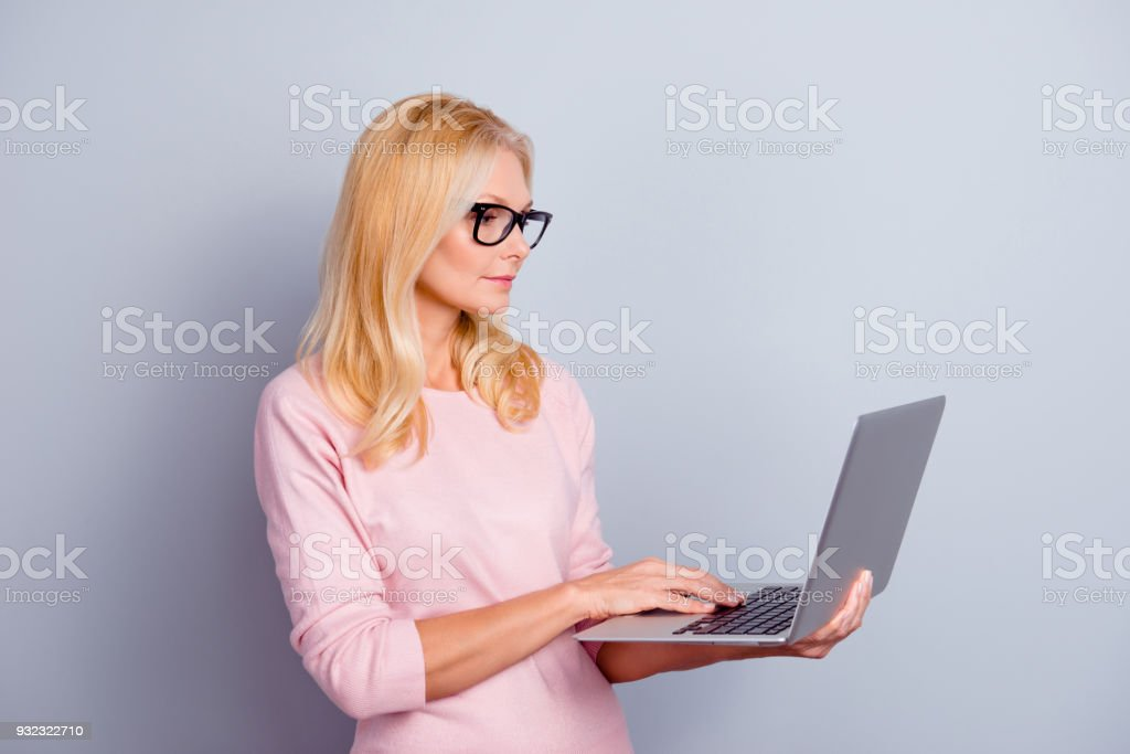 People digital pc device gadget person concept. Side half-turned view portrait of serious clever concentrated focused confident charming woman using netbook isolated on gray background copy-space stock photo