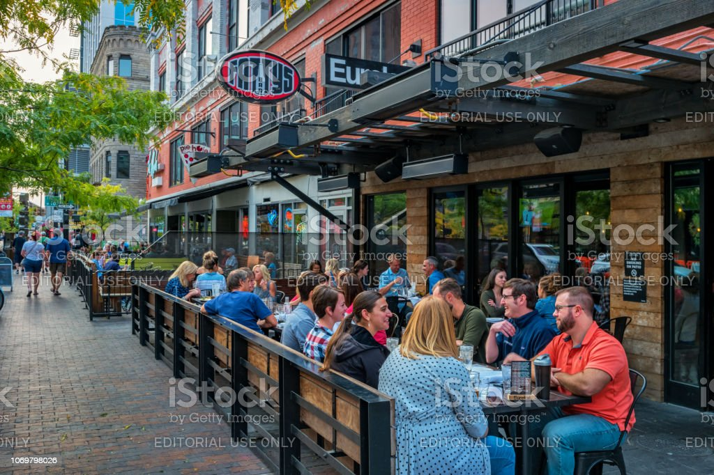 People dine at restaurant patio in downtown Boise Idaho USA People dine at a restaurant patio in downtown Boise Idaho USA in the evening. Boise Stock Photo