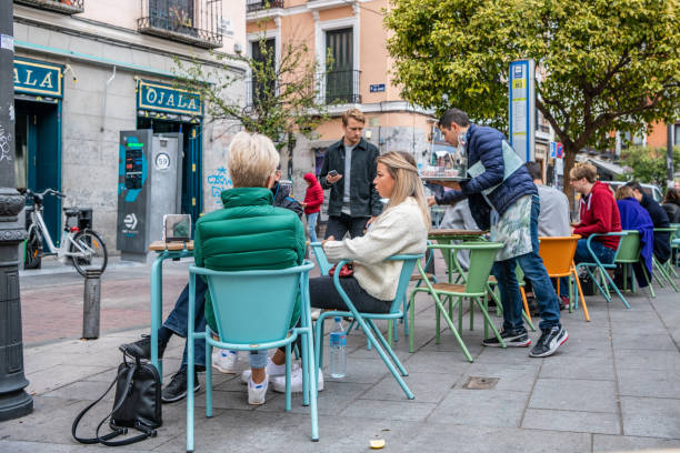 People dine out on the terrace in the popular Malasana neighborhood in Madrid. stock photo