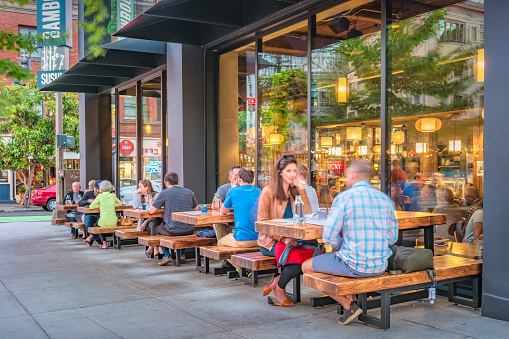 People dine on a restaurant patio in downtown Portland Oregon USA in the evening.