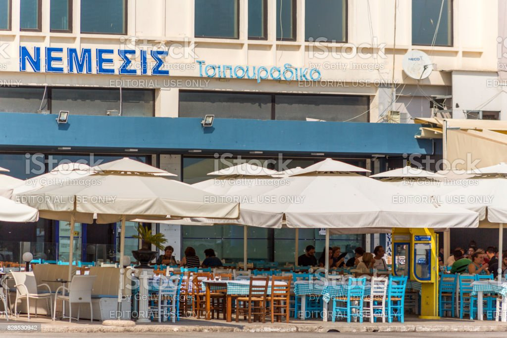 People dining at restaurants near coast of historical city with small houses at kavala greece