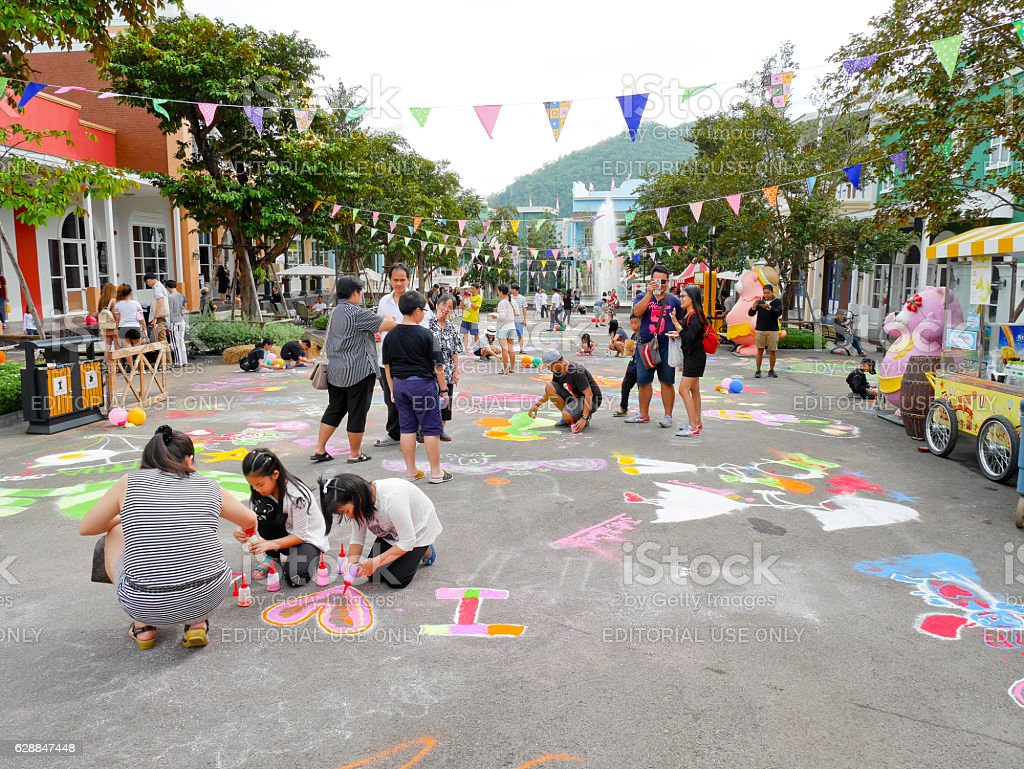 People do colorful sand art on the street stock photo