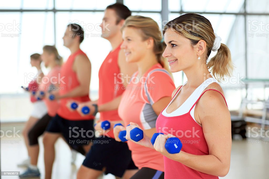 People doing exercise with dumbbells in the sport club. royalty-free stock photo