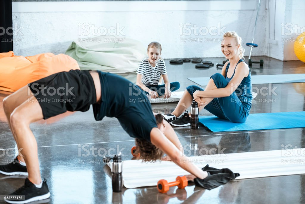 People doing gymnastics, man performing bridge pose at fitness studio royalty-free stock photo