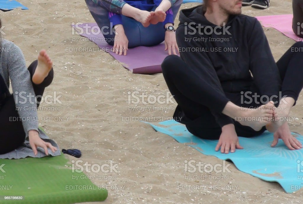 People Doing Outdoors Physical Yoga Exercise For Health And Relaxation - Royalty-free Beach Stock Photo