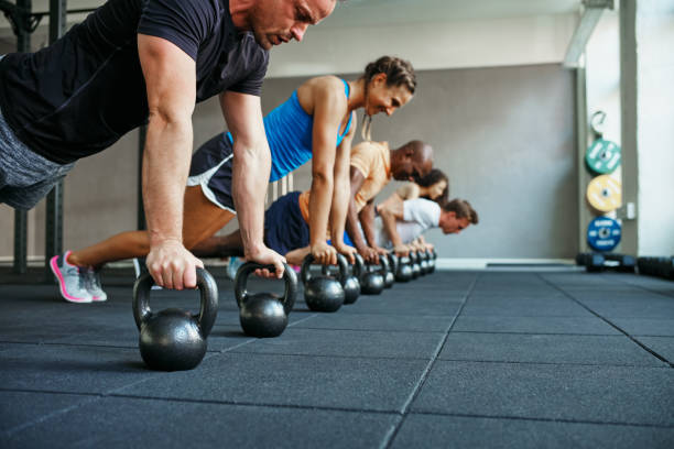 Pessoas fazendo flexões juntos em uma classe de clube de saúde - foto de acervo