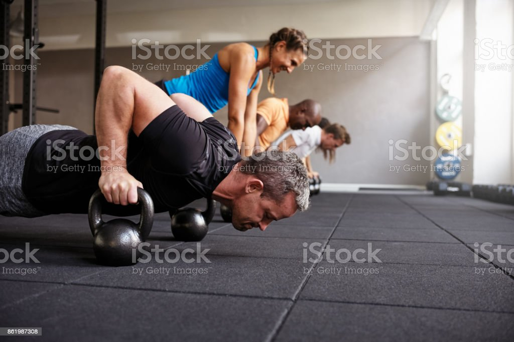 People doing pushups together in a health club class stock photo