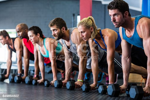 1069872470istockphoto People doing push-ups with dumbbell in gym 649864502