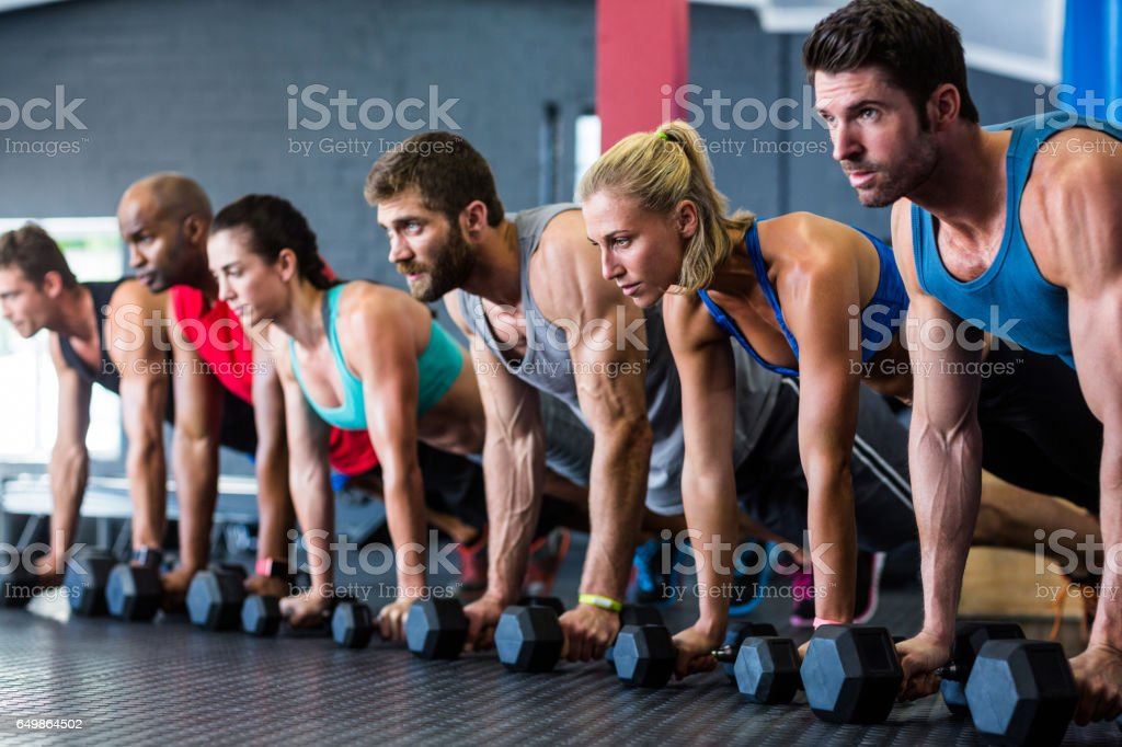 People doing push-ups with dumbbell in gym stock photo