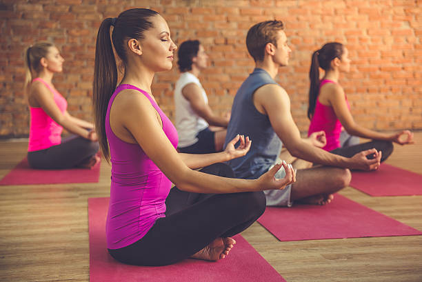 People doing yoga Side view of beautiful sports people sitting in lotus position while doing yoga in modern fitness hall yoga studio stock pictures, royalty-free photos & images