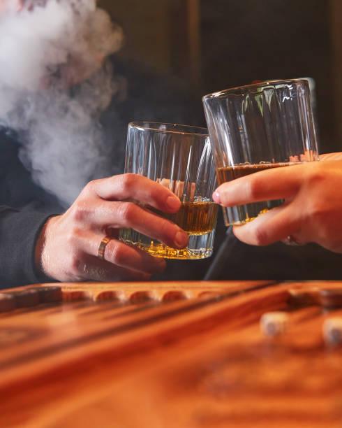People drinking whiskey, smoking hookah and playing backgammon. stock photo