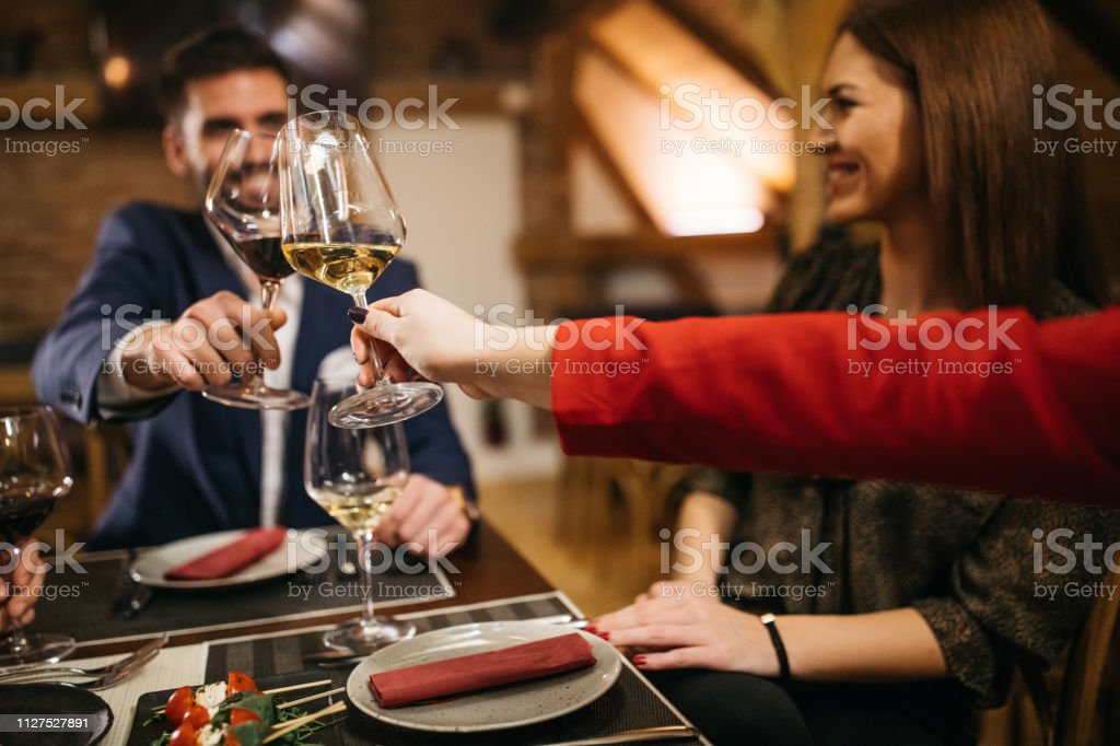 Group of people, men and women, sitting in restaurant together.