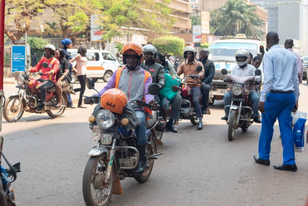 People drive their motorcycles down a street in Kampala, Uganda. stock photo