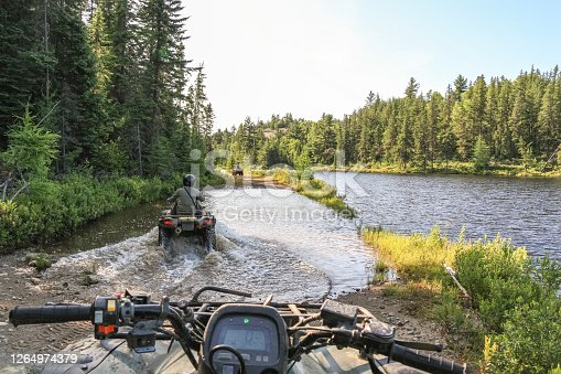 istock People driving ATV quadbike through water. Lake in Ontario, Canada. 1264974379