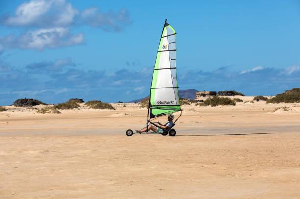 people driving sand yachting on the beach. - kitesurfen lernen stock-fotos und bilder