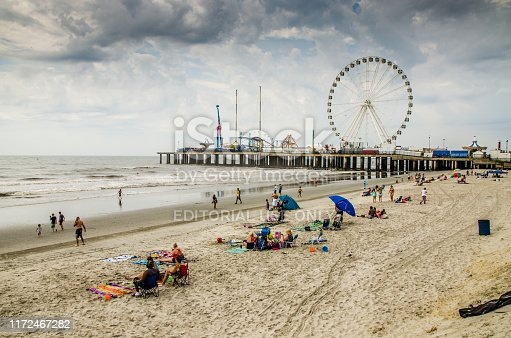 People on beach during cloudy day at Atlantic city in the morning of summer Amusement park in background