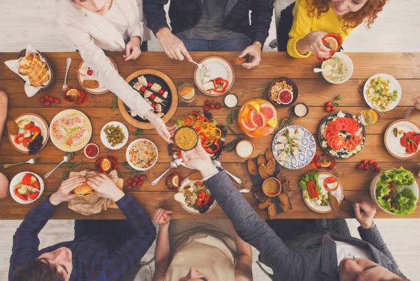 Las personas comen comidas saludables en la mesa de la cena se sirven - foto de stock