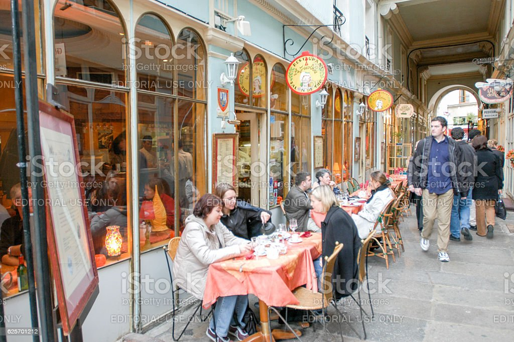 People eating and drinking in a street restaurant of Paris stock photo