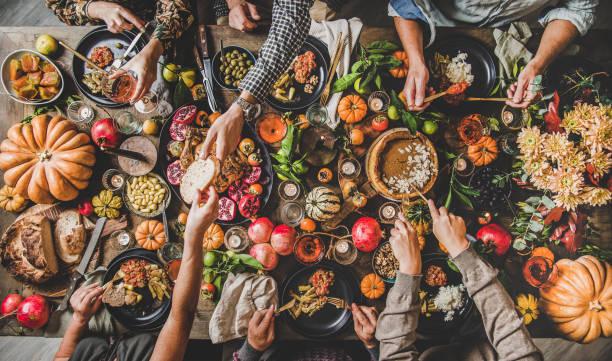 people eating and drinking wine at thanksgiving celebration dinner table - kolacja spotkanie towarzyskie zdjęcia i obrazy z banku zdjęć