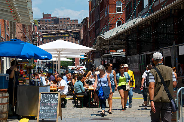 People eating at outdoor tables,Seaport District, Lower Manhattan, NYC New York City, USA - June 20, 2013: Tourists are seen passing by people eating and relaxing at outdoor cafe style seating along Front Street at the Fulton Market-South Street Seaport District in Lower Manhattan. south street seaport stock pictures, royalty-free photos & images