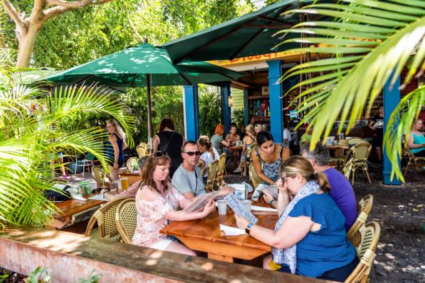 menschen, die essen in tropischen restauranttischen im dschungel-stil touristen in florida auf reisen, sonnigen tag, bar namens blue macaw island eats - urbanara stock-fotos und bilder