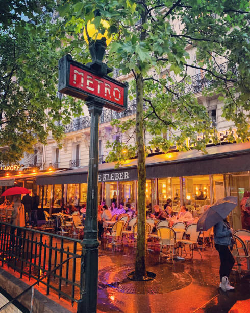 People eating outside and inside of restaurant in Paris under rain, France stock photo