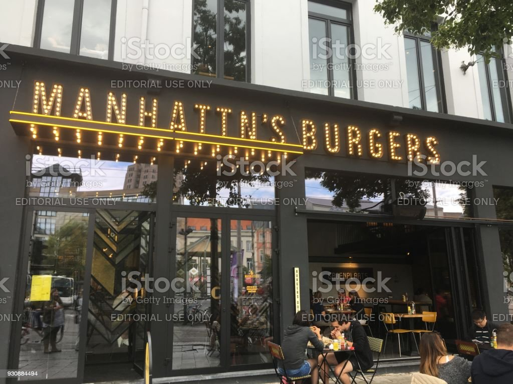 People eating outside at Manhattan's Burgers in Antwerp. People sitting down at tables outside eating American style fast food in Belgium. stock photo