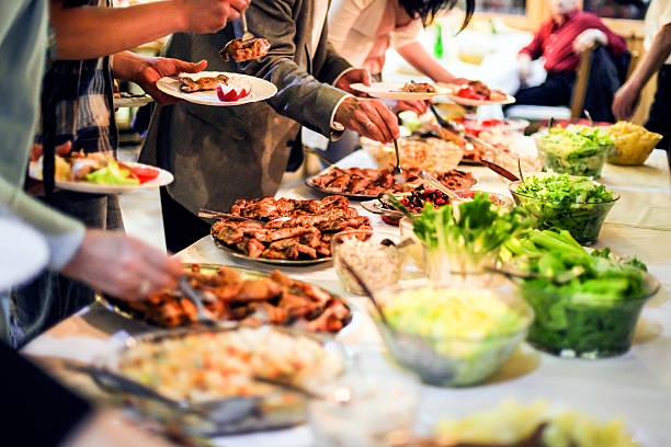 People eating Large group of people picking food (grilled meat and salads) from a buffet table. Unrecognizable Caucasian adults, both female and male. buffet stock pictures, royalty-free photos & images