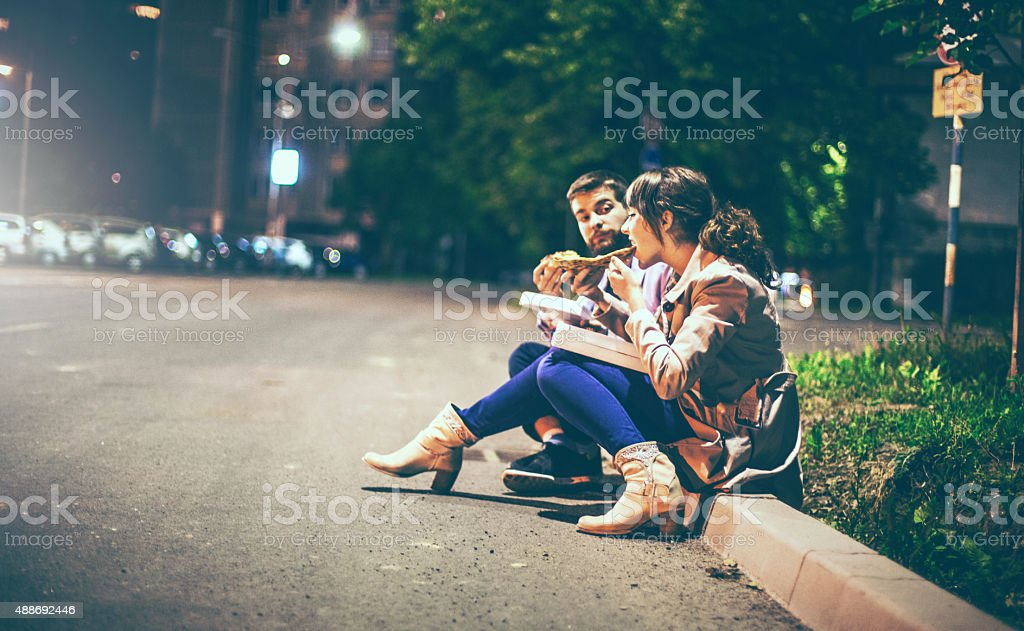 People eating pizza in the street. stock photo