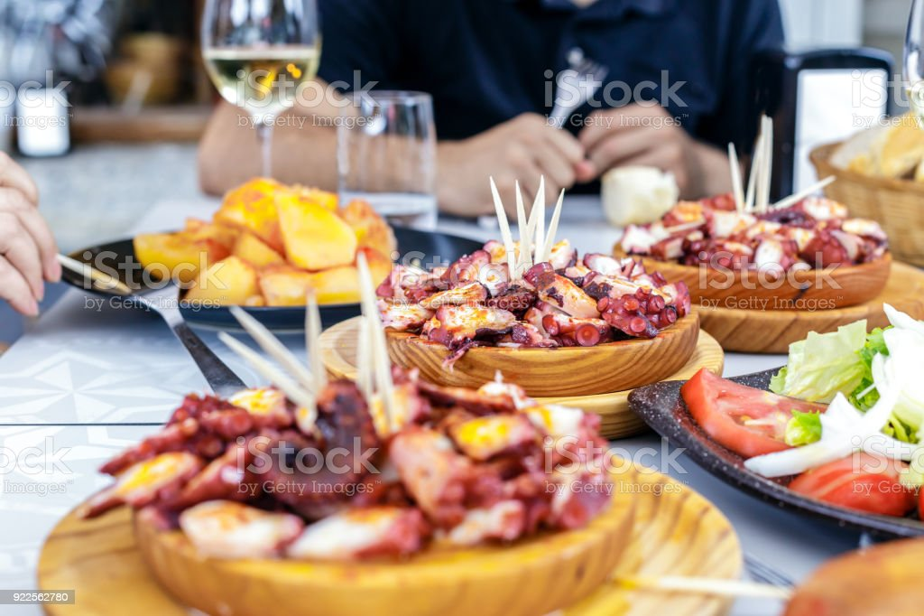 People eating Pulpo a la Gallega with potatoes. Galician octopus dishes. Famous dishes from Galicia, Spain. stock photo