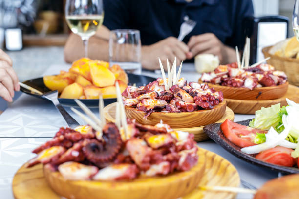 people eating pulpo a la gallega with potatoes. galician octopus dishes. famous dishes from galicia, spain. - spain stock pictures, royalty-free photos & images