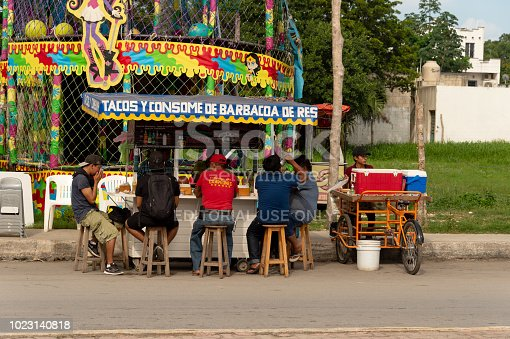 istock People eating tacos at a colorful mexican food stand. 1023140818