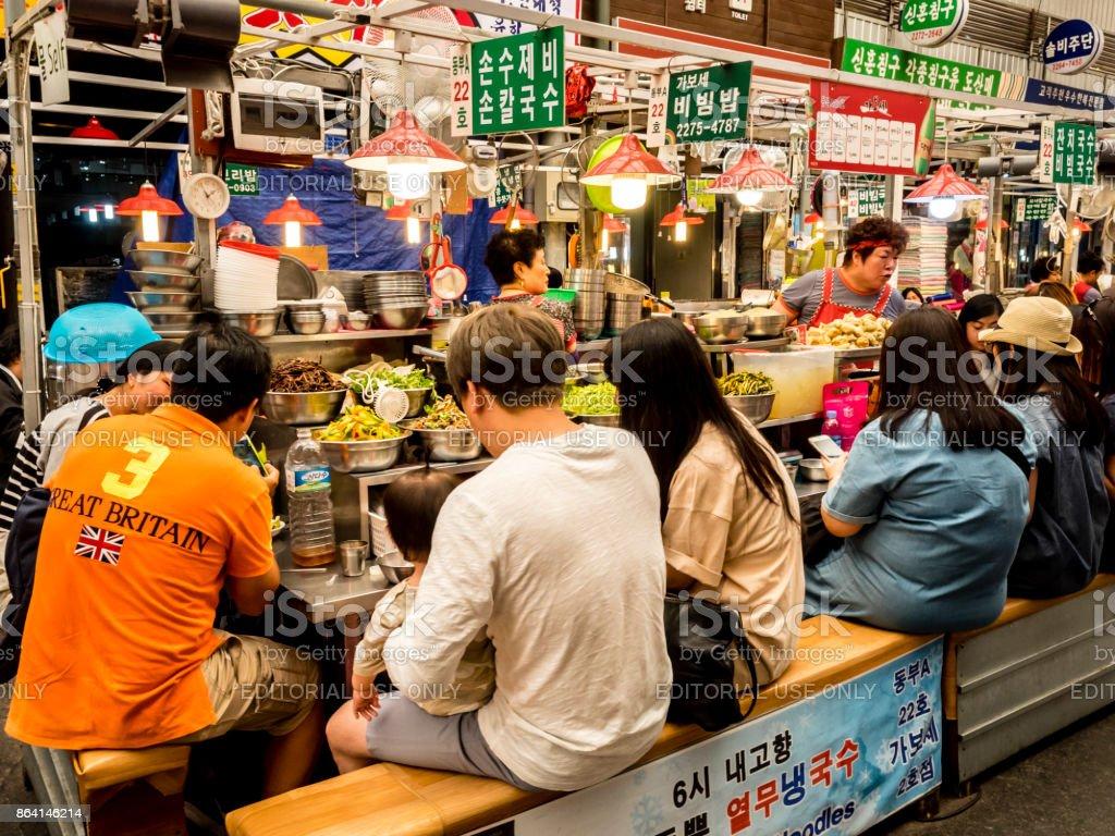 People eating tasty food and drink at Gwangjang Market in Seoul. royalty-free stock photo