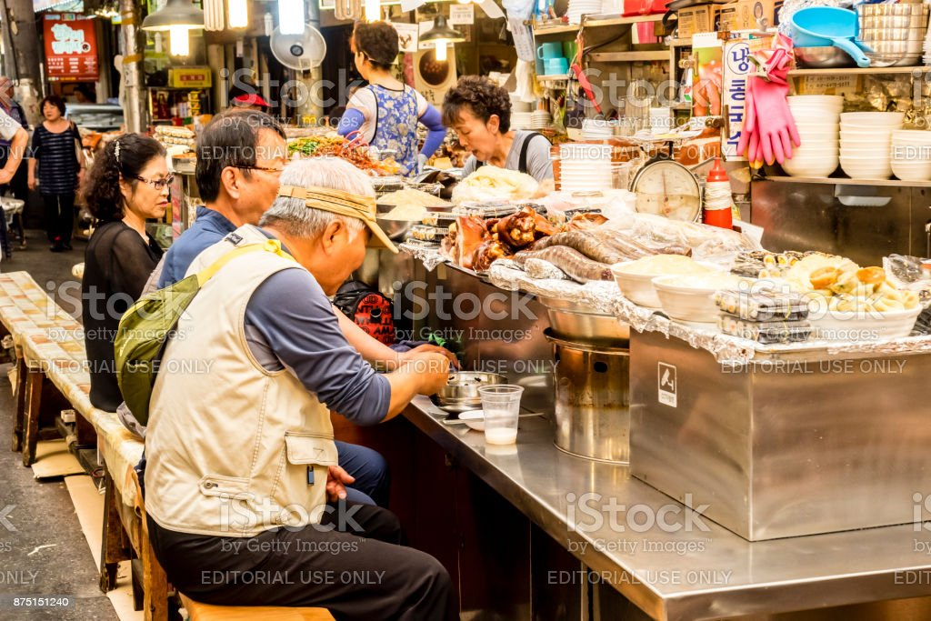 People eating tasty food and drink at Gwangjang Market in Seoul. stock photo