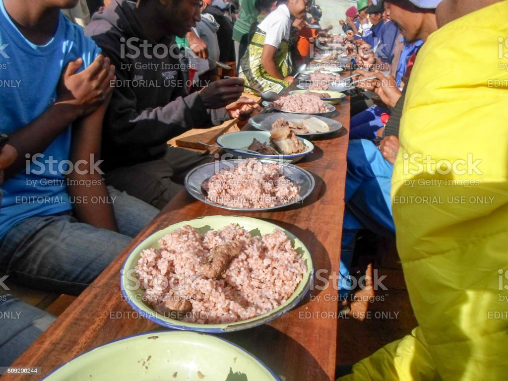People Eating The Famous Traditional Malagasy Dish Of Red Rice And Pork Called Locally Henakisoa Sy Vary Be Menaka Stock Photo Download Image Now