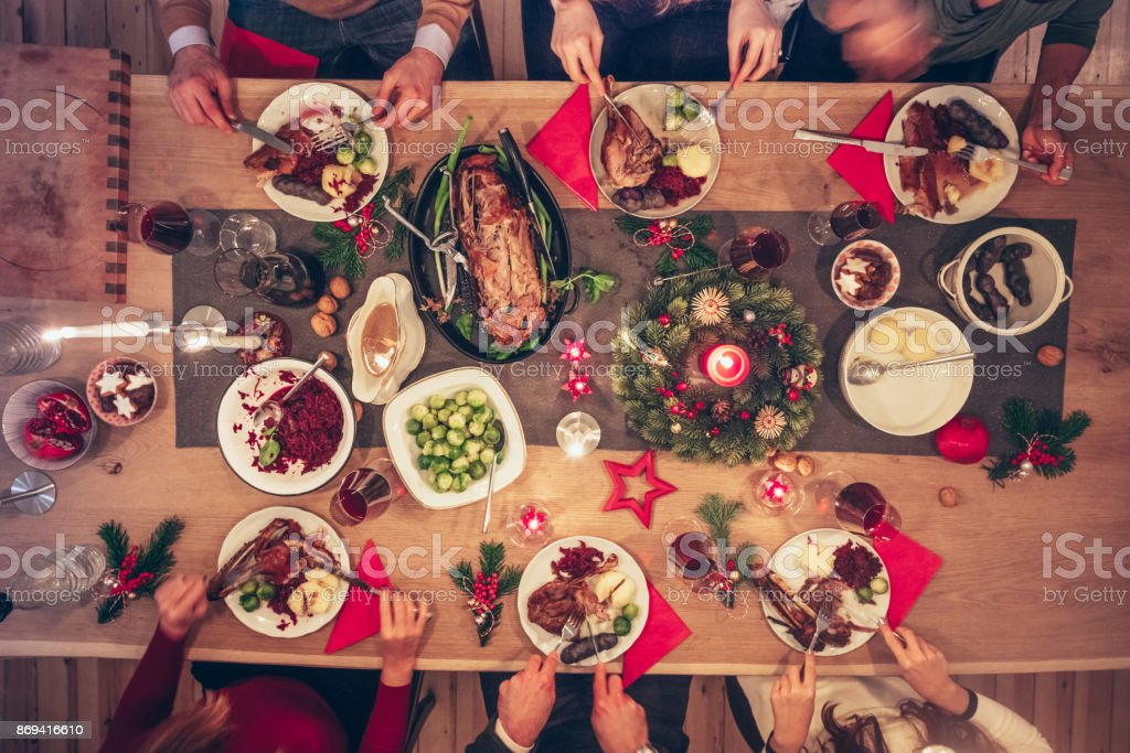 people eating traditional christmas meal at festive wooden table stock photo