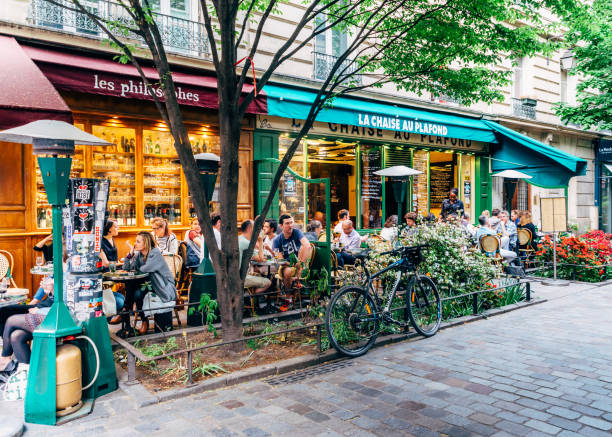 People enjoy a cafe and conversation at a quiet and charming tree-lined street in the bohemian Marais district of Paris, France during the spring stock photo