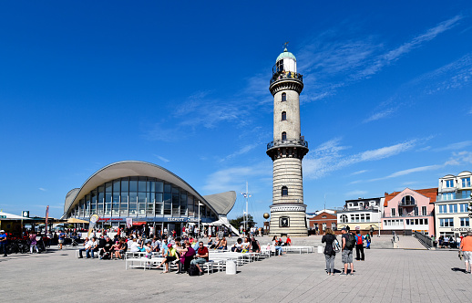 People enjoy a summer day at the lighthouse and at the landmark Teepot in the Baltic Sea resort of Warnemünde