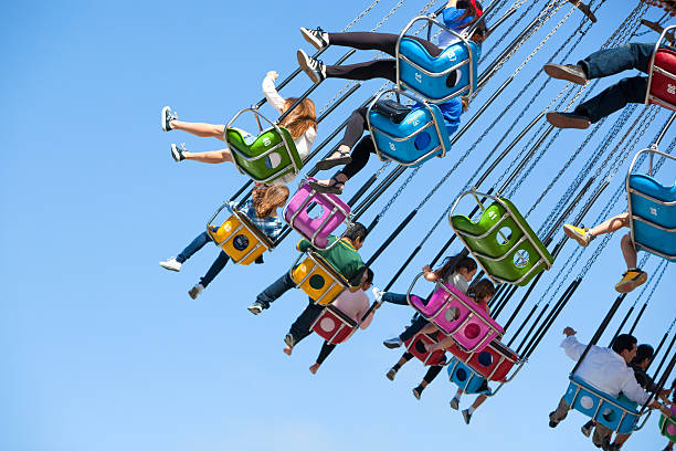 People Enjoy a Swing Ride at an Amusement Park stock photo