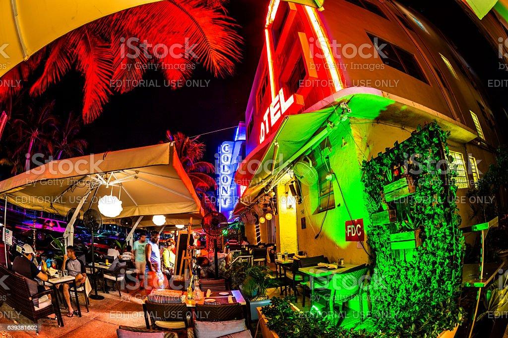 people enjoy bar and restaurant at night at Ocean drive stock photo
