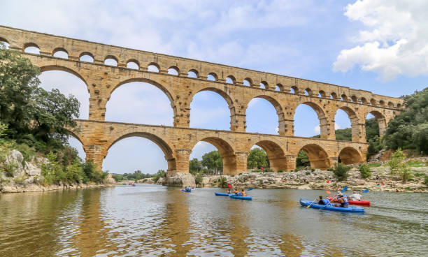 People enjoy canoeing in summer under the Pont Gard stock photo