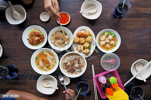 546450250istockphoto people enjoy eating many of traditional chinese asian food noodle, soup, deep-fried fish ball, photography from top view on wooden table 849196384