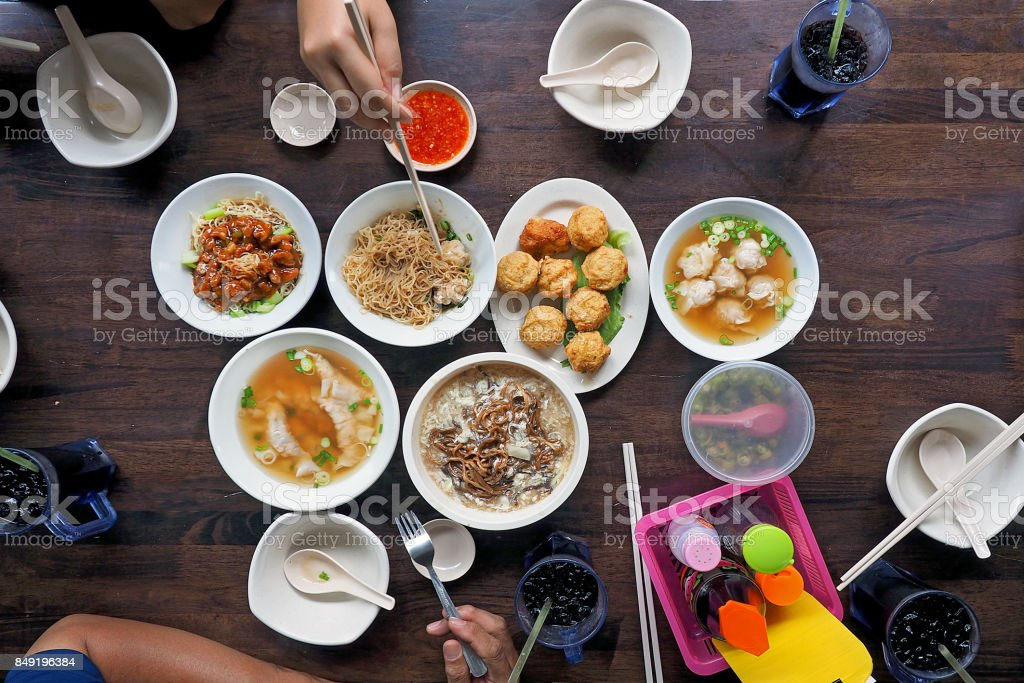 people enjoy eating many of traditional chinese asian food noodle, soup, deep-fried fish ball, photography from top view on wooden table stock photo