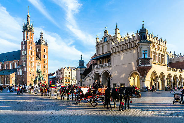people enjoy Horse carriages in front of Mariacki church stock photo