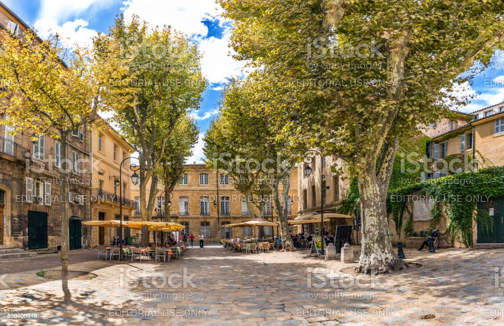 people enjoy resting at a tree covered place in the  old town of charming Aix en Provence stock photo