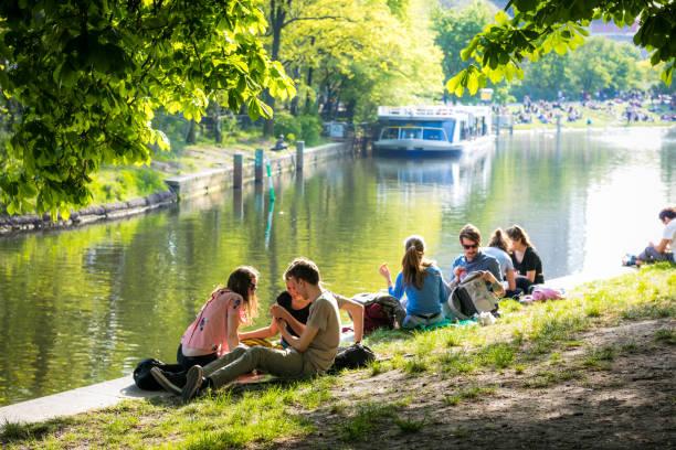 menschen genießen sie sonne am landwehrkanal in berlin kreuzberg - kreuzberg stock-fotos und bilder