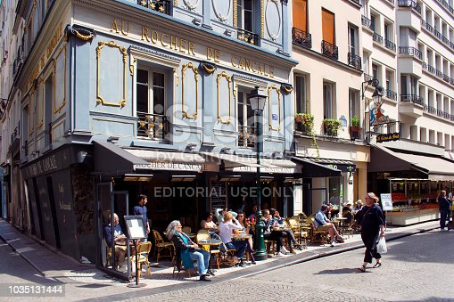People enjoy sunny weather at a traditional bistro / cafe on one of famous streets (Rue Montorgueil) in Paris. Woman passes by.