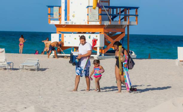 People enjoy the beach next to a lifeguard tower stock photo
